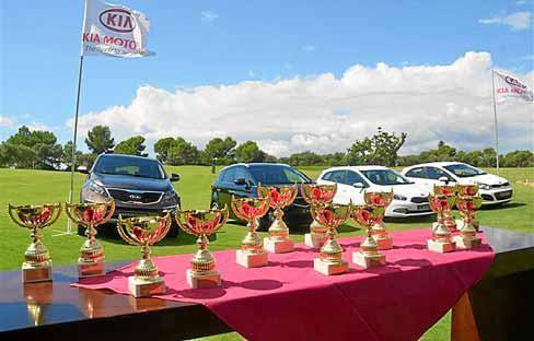 Los trofeos que se repartieron al acabar el torneo con la gama Kia expuesta en el campo de golf.