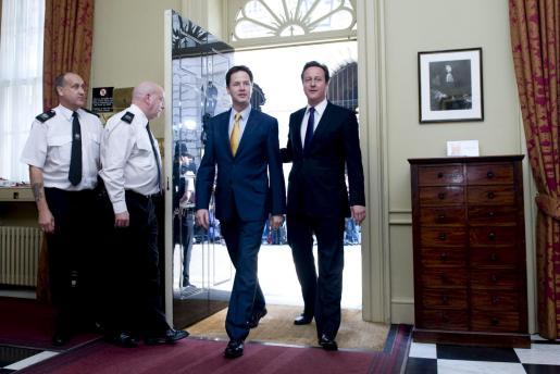 El nuevo primer ministro británico, David Cameron (d), y el viceprimer ministro, el liberaldemócrata Nick Clegg (2d), entran en la residencia oficial del primer ministro británico.