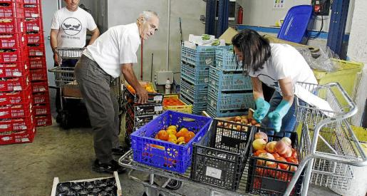 Voluntarios organizando la distribución de comida en cajas para posteriormente ser transportada.