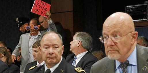 Las protestas acompañaron a Keith Alexander (i) durante una audiencia ante el Comité de Inteligencia del Congreso de Estados Unidos.