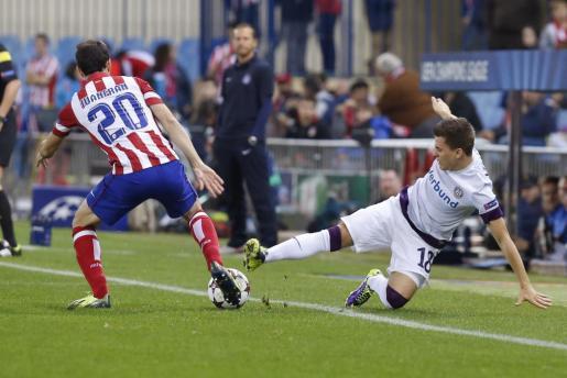 El defensa del Atlético de Madrid Juanfran Torres (i) pelea un balón con el centrocampista del Austria de Viena Thomas Murg.