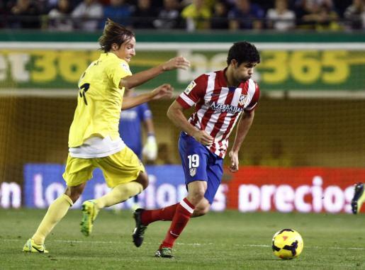 El centrocampista del Villarreal Tomás Pina (i) pelea un balón con el delantero del Atlético de Madrid Diego Costa.