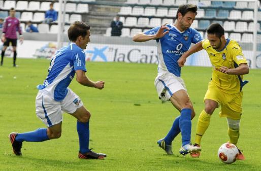 Florín Andone controla un balón ante la presencia de dos jugadores del Lleida.