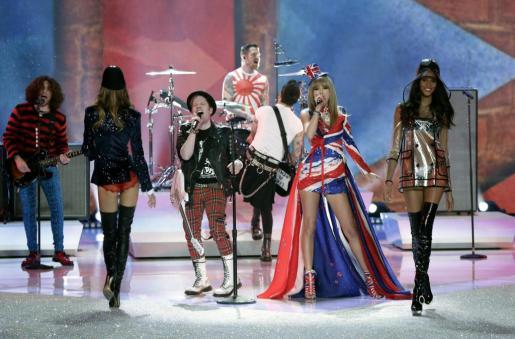 La modelo puertorriqueña Joan Smalls camina por la pasarela mientras la cantante estadounidense Taylor Swift (c) y su banda Fall Out Boy se presentan durante el desfile de la marca de lencería Victoria's Secret.