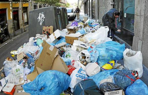 A man closes his shop next to garbage strewn on the pavement on the ninth day of an indefinite strike by street cleaners in Madrid November 14, 2013. Spain's labour unions called for an indefinite strike in Spain's capital last Tuesday for the street cleaning and park maintenance sectors in protest against announced layoffs that could affect over a thousand municipal workers, according to local media. REUTERS/Juan Medina (SPAIN - Tags: BUSINESS EMPLOYMENT CIVIL UNREST SOCIETY ENVIRONMENT POLITICS) SPAIN-GAR