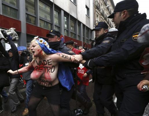 Agentes de la Policía Nacional intentan evitar que las activistas de Femen interfieran en la manifestación.