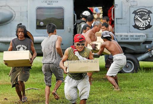 Afectados por el tifón 'Haiyán' cargan cajas tras la llegada de un helicóptero con ayuda.