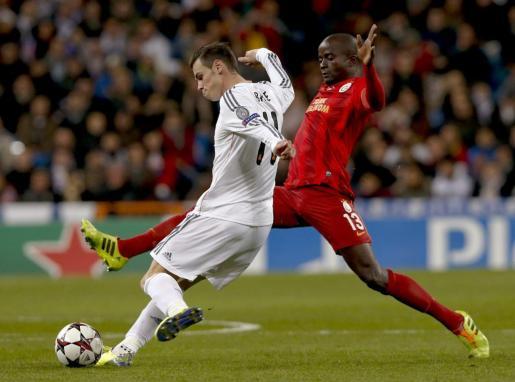 El delantero galés del Real Madrid Gareth Bale (i) dispara ante el defensa camerunés del Galatasaray turco Dany Nounkeu (d).