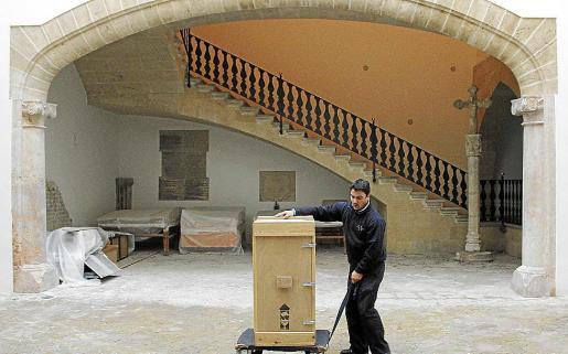 Un operario transporta un embalaje con una obra de arte en el patio del museo.