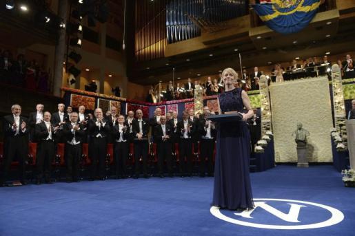 Jenny Munro, hija de la premio Nobel de Literatura 2013 Alice Munro, sostiene el galardón durante la ceremonia de entrega de los Premios Nobel.