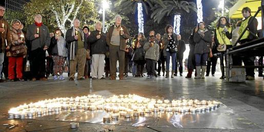 Cerca de un centenar de personas participó en el acto, que contó con el tradicional encendido de velas. Fotos: TERESA AYUGA