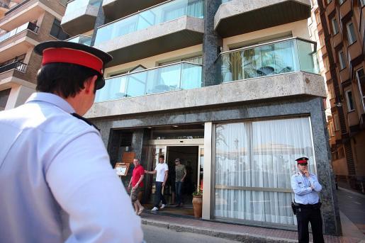 Varios mossos de squadra vigilan la puerta del hotel donde han sido encontrados los dos niños británicos muertos.