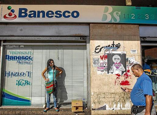 Una mujer, ayer, en la entrada de una oficina de Banesco en el centro de Caracas.