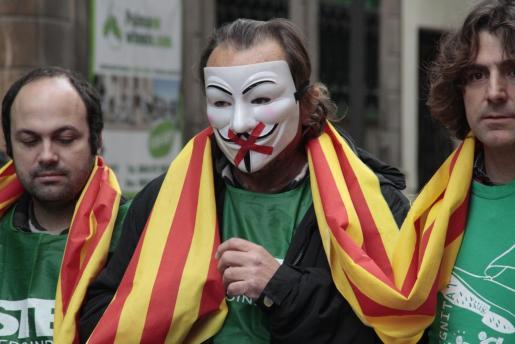 Un manifestante, con careta que representa el recorte a la libertad de expresión, a las puertas del Parlament, donde hoy se aprueba la Llei de Símbols.