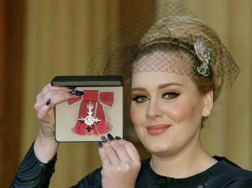 Adele muestra la insignia recibida hoy en el palacio de Buckingham.