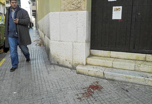Un peatón observa los restos de sangre de la víctima en el lugar donde fue apuñalada.
