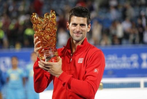 El serbio Novak Djokovic posa junto al trofeo obtenido en Abu Dhabi.