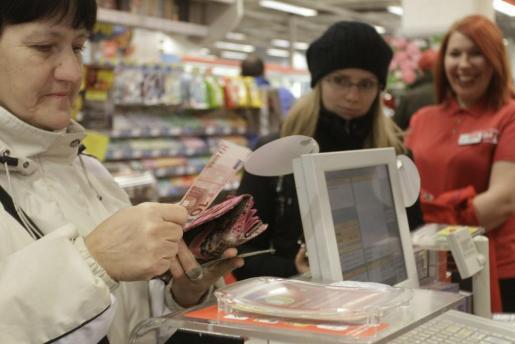 Una mujer paga con un billete de 10 euros en un supermercado en Riga, Letonia.