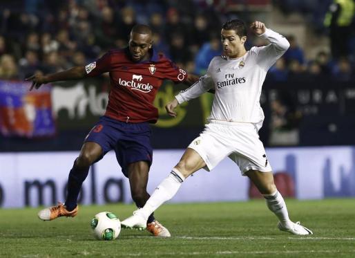 El centrocampista francés de Osasuna Raoul Loé (i) intenta conseguir la posesión del balón ante el delantero portugués del Real Madrid Cristiano Ronaldo (d).