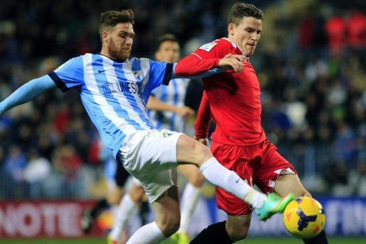 El lateral portugués del Málaga Vitorino Antunes (i) pelea un balón con el francés Kevin Gamero, del Sevilla.