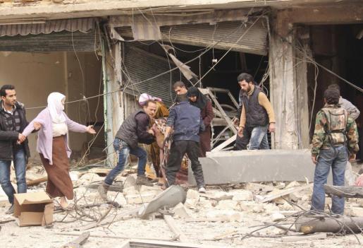 Varias personas ayudan a una a salir de un edificio derruido.