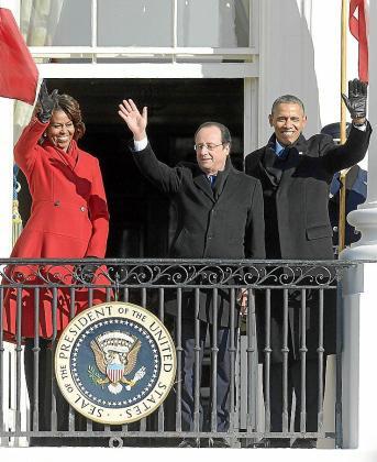 Obama, su mujer y Hollande (c) saludan desde un balcón de la Casa Blanca.