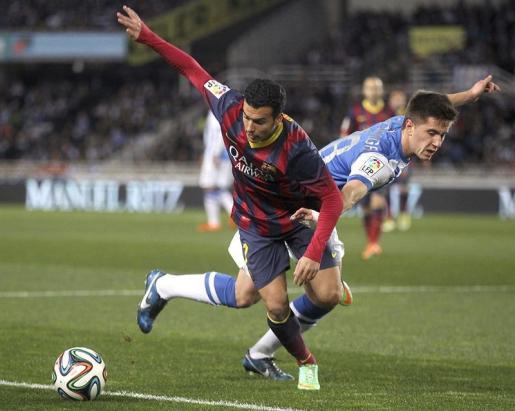 El centrocampista de la Real Sociedad Jon Gaztañaga (d) pelea un balón con Pedro, del FC Barcelona.