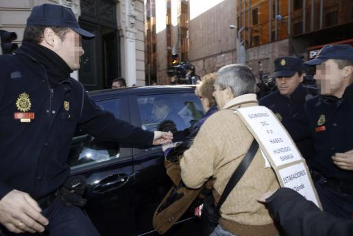 El expresidente de Caja Madrid Miguel Blesa ante diversos preferentistas y agentes de la policía, es trasladado en coche a su salida de la Audiencia Nacional.