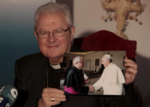 El obispo muestra la imagen que se tomó junto al Papa durante su visita a El vaticano.