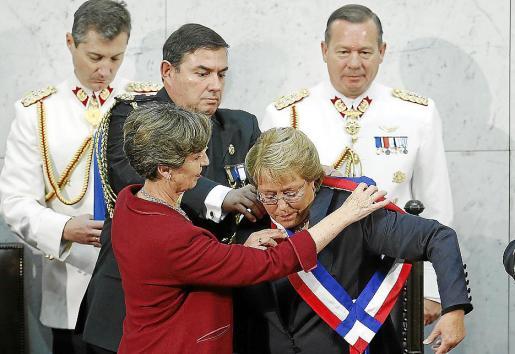 Bachelet recibe la banda presidencial de manos de la nueva presidenta del Senado, Isabel Allende.