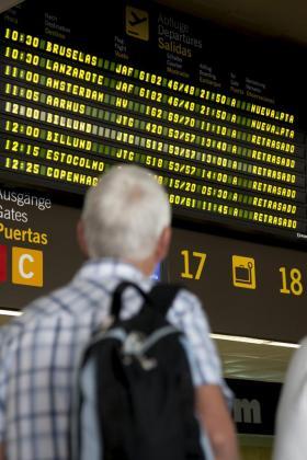 Un hombre observa los retrasos generalizados en el panel de vuelos.