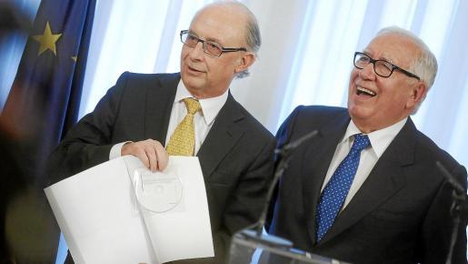 El ministro Montoro muestra el informe con 270 cambios tributarios entregado por el presidente del comité de expertos, Manuel Lagares (d).