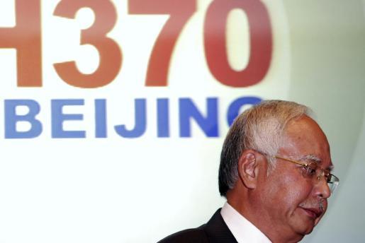 El primer ministro deMalasia, Najib Razak, abandona la sala en la que compareció para hablar del avión desaparecido.