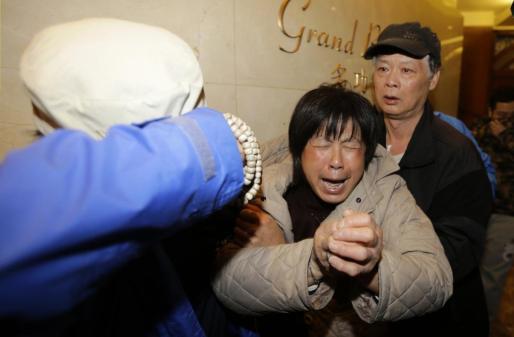 El familiar de un pasajero del avión malasio estrellado llora tras escuchar por televisión en un hotel de Pekín las últimas noticias sobre el siniestro.