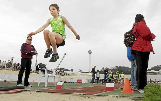 Un joven salta al foso de arena en la prueba de longitud