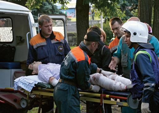 Miembros del Ministerio Ruso de Emergencias ayudan a un hombre herido durante una explosión en Stávropol.