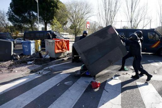 Efectivos de la Policía Nacional retiran varios de los contenedores utilizados como barricadas por un grupo de estudiantes frente a la facultad de Filosofía y Letras en la Universidad Complutense de Madrid.