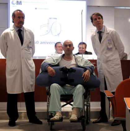 El paciente que ha sido sometido al trasplante de brazos junto a dos de los cirujanos.