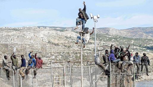 African migrants sit on top of a border fence between Morocco and Spain's north African enclave of Melilla during their latest attempt to cross into Spanish territory, April 3, 2014. Spain has more than doubled the strength of security forces at Melilla, after about 500 people stormed its fences in the biggest border rush for years earlier this month. Immigrants from all over Africa regularly dare the razor-wire fences of Spanish enclaves Ceuta and Melilla, which are surrounded by Moroccan territory and sea