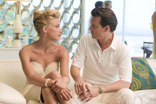"""Fotograma donde aparece el actor Johnny Depp (d), en el papel de Paul Kemp, y la actriz Amber Heard, en el papel de Chenault, durante una escena de la película """"The Rum Diary""""."""