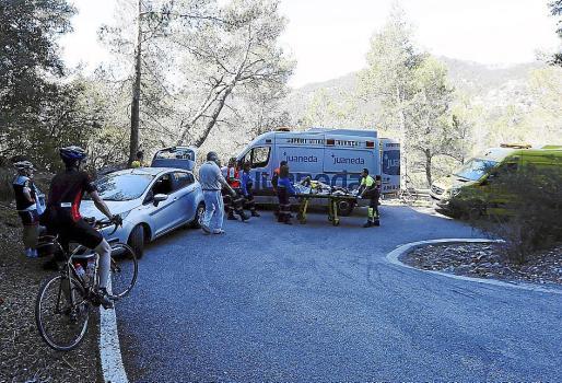 Los sanitarios asisten al herido en la curva donde ocurrió el accidente.