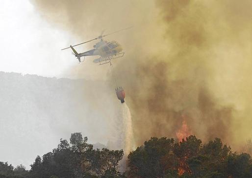 Un helicóptero del Ibanat descarga sobre el Torrent den Pujolet. Las llamas fueron ascendiendo por este torrente, donde se cree que comenzó el incendio, gracias a rachas de viento localmente fuertes.