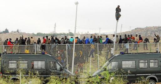 GRA051 MELILLA, 01/05/2014.- Los inmigrantes subsaharianos que permanecían encaramados a la valla de Melilla, tras protagonizar un intento de entrada masivo a la ciudad, se han bajado del obstáculo fronterizo tras haber permanecido subidos en él más de seis horas. Los inmigrantes han ido descendiendo por la valla ante la presencia de un fuerte dispositivo policial y han sido entregados a las autoridades marroquíes, que se encontraban al otro lado del vallado. EFE/Paco Guerrero