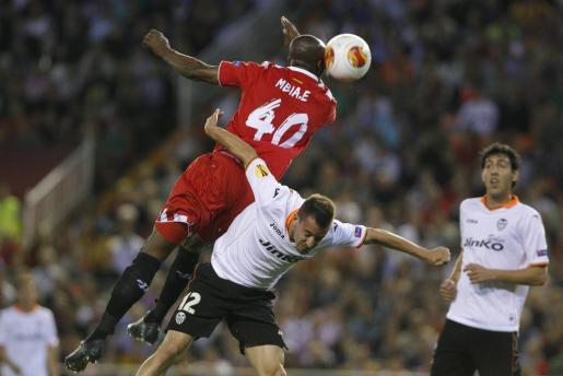 El defensa portugués del Valencia CF Joao Pereria (c) lucha el balón con el camerunés Stéphane Mbia (i), del Sevilla FC.