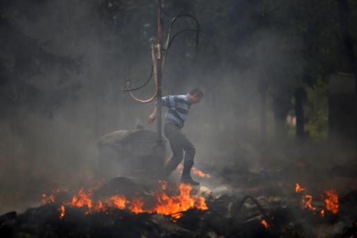 Un hombre salta sobre una barricada en llamas en Mariúpol.