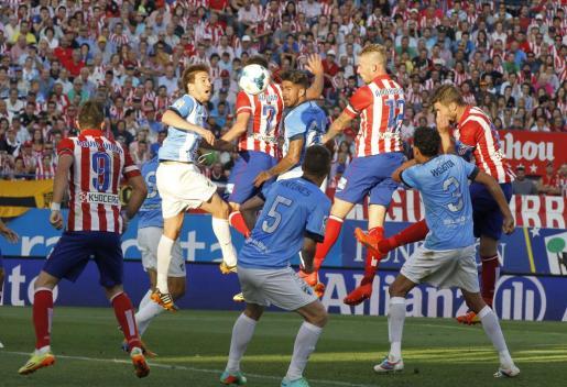 El defensa belga del Atlético de Madrid Toby Alderweireld (3d) remata de cabeza para marcar el 1-1 ante el Málaga.