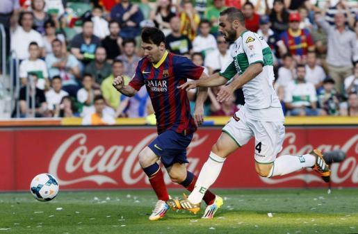El delantero argentino del FC Barcelona Lionel Messi (i) avanza con el balón ante el defensa del Elche David Lombán (d).