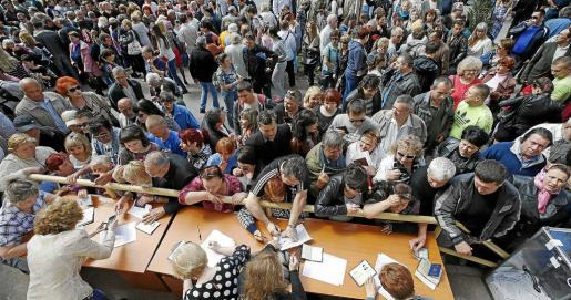 People stand in a line to receive ballots from members (front) of a local election commission during the referendum on the status of Donetsk region in the eastern Ukrainian city of Mariupol May 11, 2014. East Ukrainian rebels pressed ahead with a referendum on self-rule on Sunday and new fighting flared in a conflict that has raised fears of civil war and pitched relations between Russia and the West into their worst crisis since the Cold War. REUTERS/Marko Djurica (UKRAINE - Tags: POLITICS CIVIL UNREST EL