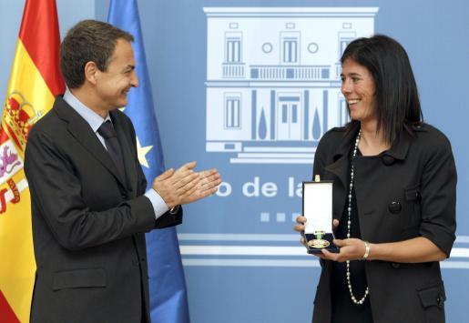 El presidente del Gobierno, José Luis Rodríguez Zapatero, aplaude tras entregar a la montañera Edurne Pasabán la medalla de oro al mérito deportivo.