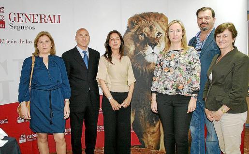 """Isabel Baeza, José Baeza, Britt Revuelta, Bárbara Prohens, Juan Manuel Serra y Margarita Dahlberg ante la imagen del """"león de los seguros"""" que preside la oficina."""